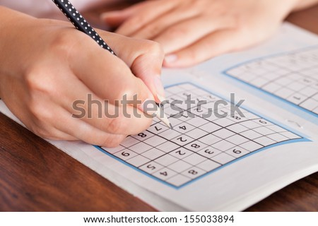 Close-up Of Woman Hand Solving Sudoku With Pen - stock photo