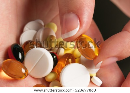 Close-up of woman hand with colorful pills