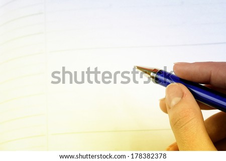 Close-up of woman hand writing in agenda - stock photo