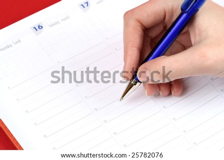 Close-up of woman hand writing in agenda