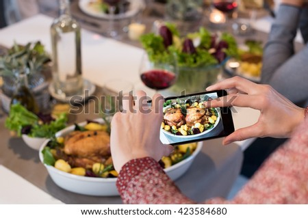 Close up of woman hands clicking picture of food. Woman using smartphone for food photography. Close up of female hands taking photo of roasted chiken with smart phone.  - stock photo