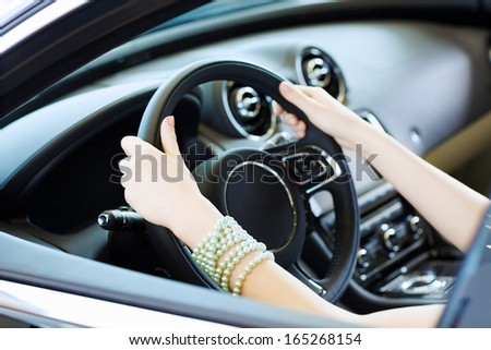 Close up of woman hands driving a car - stock photo