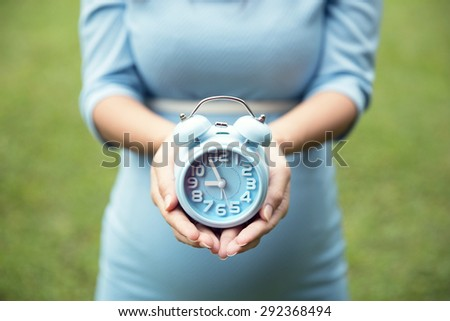 close up of woman hands holding an blue alarm clock, grass background - stock photo
