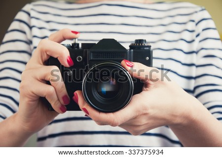 Close up of woman hands holding retro camera - stock photo