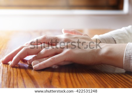 Close-up of woman hands in reflexive and concern position on wooden table. Concepts of security, tranquility, waiting for and others