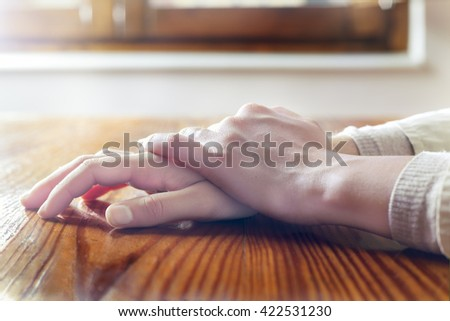 Close-up of woman hands in reflexive and relaxing position on wooden table. Concepts of security, tranquility, waiting for and others