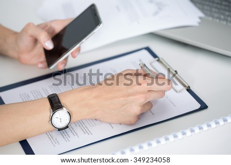Close up of woman hands looking something at mobile phone and filling documents