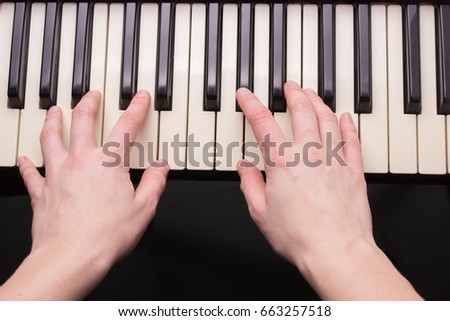Close up of woman hands playing electronic piano