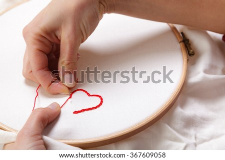 Close up of Woman Hands sewing a Red Heart Shaped Decoration on White Fabric