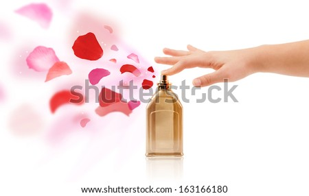 close up of woman hands spraying rose petals from beautiful perfume bottle - stock photo
