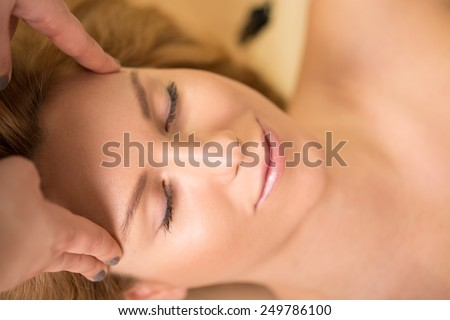 Close-up of woman having her head massaged - stock photo