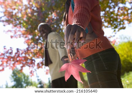 Close up of woman holding autumn leaf