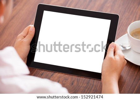 Close-up Of Woman Holding Digital Tablet In Front Of Coffee Cup - stock photo