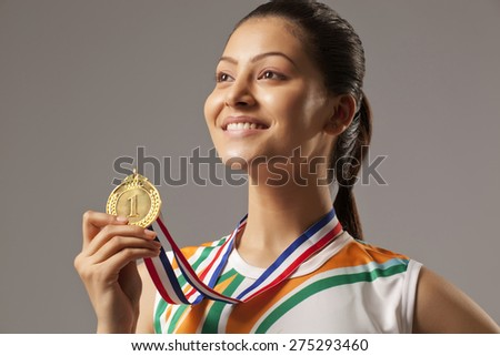 Close-up of woman holding gold medal isolated over gray background - stock photo