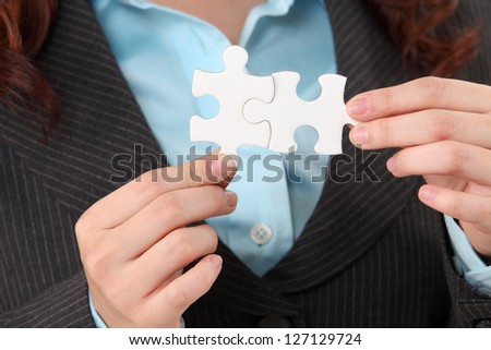 close up of woman holding puzzle pieces