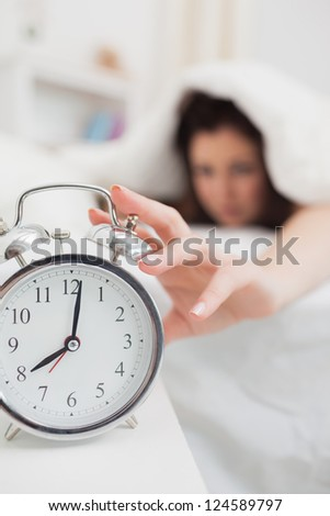 Close-up of woman in bed extending hand to alarm clock