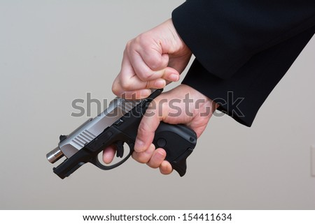 Close up of woman in business suit cocking a pistol - stock photo