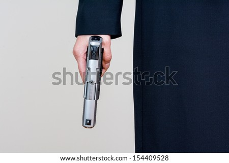 Close up of woman in business suit holding a gun front side - stock photo