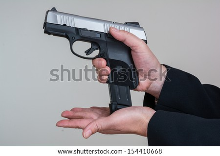 Close up of woman in business suit loading a pistol - stock photo