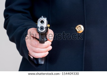 Close up of woman in business suit pointing a gun at you - stock photo
