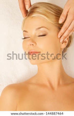 close up of woman in spa salon getting face treatment - stock photo