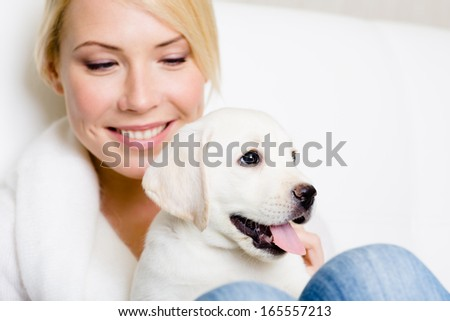Close up of woman in white sweater with labrador puppy sitting on her knees