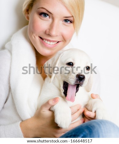 Close up of woman in white sweater with white Labrador puppy sitting on her knees and yawning