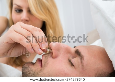 Close-up Of Woman Inserting Nose Clip Device Into Sleeping Man Nose - stock photo