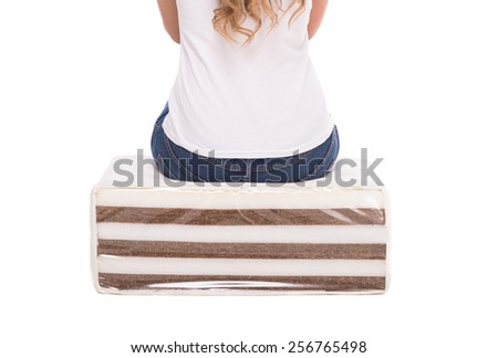 Close-up of woman is sitting on the quality mattress made of coconut fiber. - stock photo