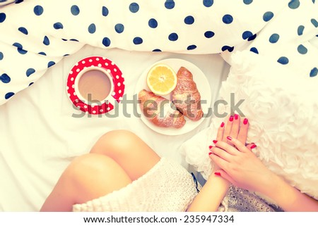 Close-up of woman legs and breakfast in bed with croissants, coffee and orange juice on a lazy sunday morning  - stock photo
