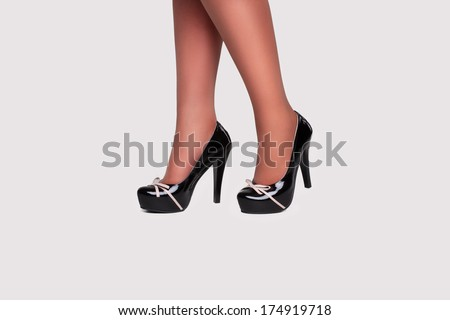close-up of woman legs in black stockings wearing suede boots on high heel - stock photo