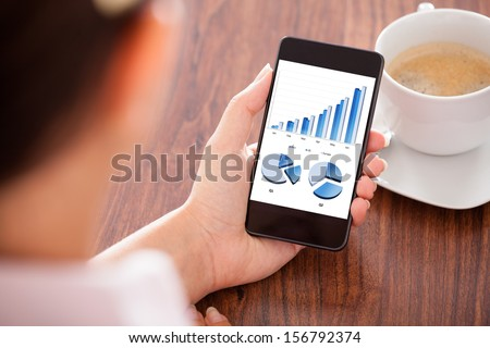 Close-up Of Woman Looking At Graph On Mobile Phone - stock photo