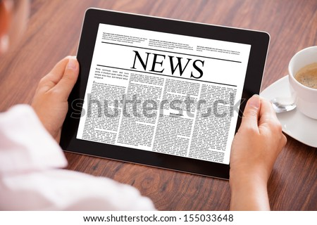 Close-up Of Woman Looking At News Article On Digital Tablet In Front Of Coffee Cup - stock photo