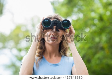 Close-up of woman looking through binocular in forest