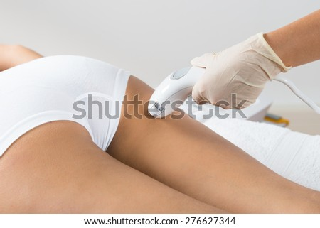 Close-up Of Woman Lying Receiving Epilation Laser Treatment On Buttock - stock photo