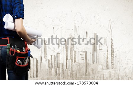 Close up of woman mechanic with project in hand against city background - stock photo