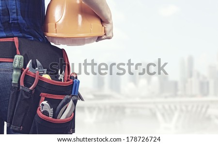 Close up of woman mechanic with yellow helmet in hand against city background - stock photo