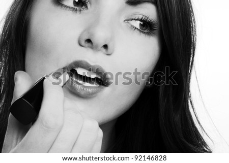 close up of woman mouth as she puts on lip stick - stock photo