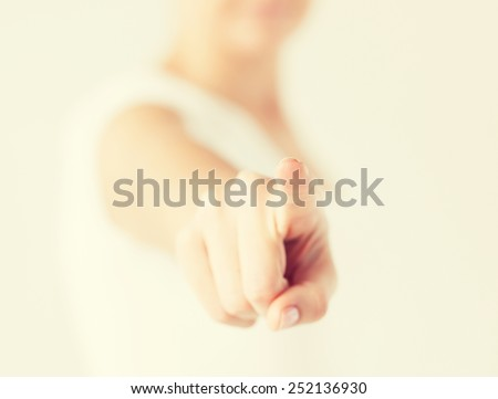 close up of woman pointing her finger at you - stock photo