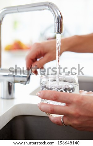 Close Up Of Woman Pouring Glass Of Water From Tap In Kitchen