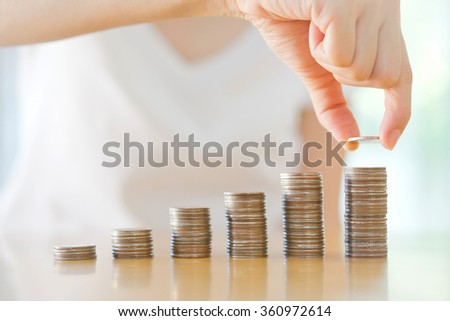 Close-up Of woman Putting Coin To Rising Stack Of Coins