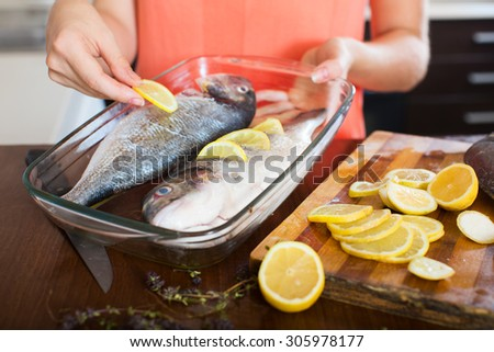 Close-up of woman putting pieces of lemon in fish at  kitchen