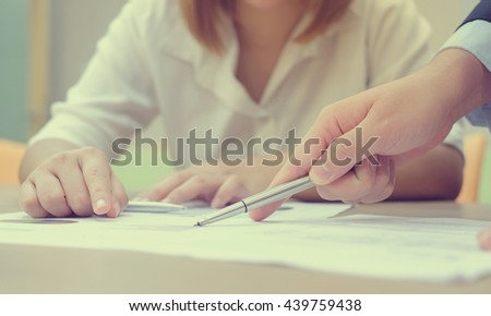 close up of woman reading understanding about business agreement on paper document application follow lawyer man suggest:business woman consulting barrister before sign signature.vintage tone effect. - stock photo