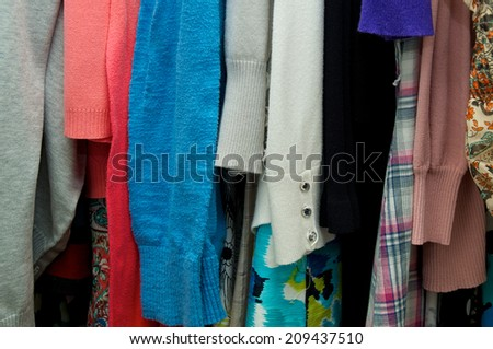 Close up of woman's clothing hanging in closet, showing various materials and colors - stock photo