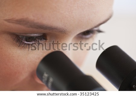 close up of woman's eyes looking through microscope - stock photo