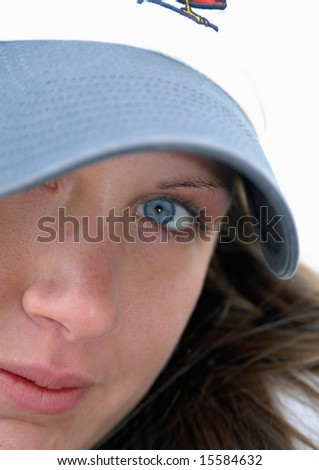 Close up of woman's face with pretty blue eye framed by bill of blue baseball cap