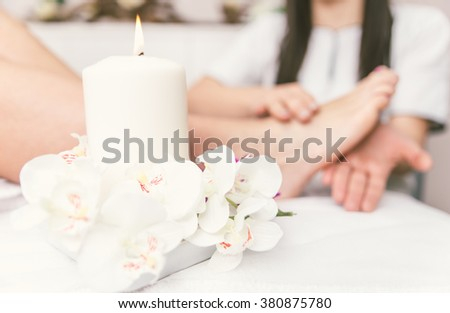 Close up of woman's feet and beauty saloon decorations. Beautician making foot massage. Concept about body care, spa and massages - stock photo