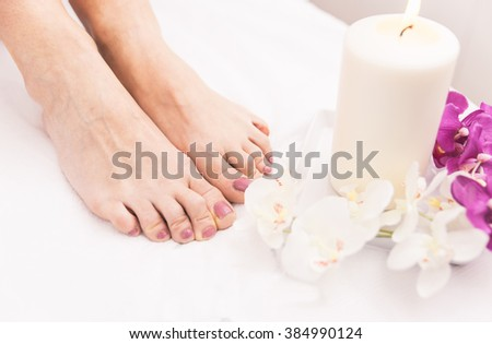 Close up of woman's feet and beauty saloon decorations. Concept about body care, spa and massages - stock photo