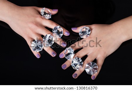 Close-up Of Woman's Hand And Diamonds Isolated On Black Background