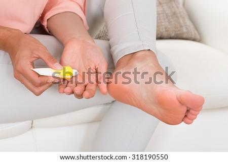 Close-up Of Woman's Hand Applying Moisturizing Cream On Foot - stock photo